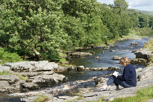 Woman reading beside a stream