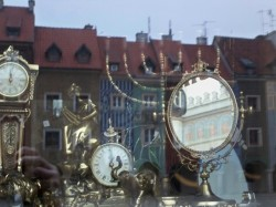 Antique shop window in Poznan with menorah (and central square reflected)
