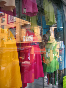 Reflections in a store window with colourful dresses.