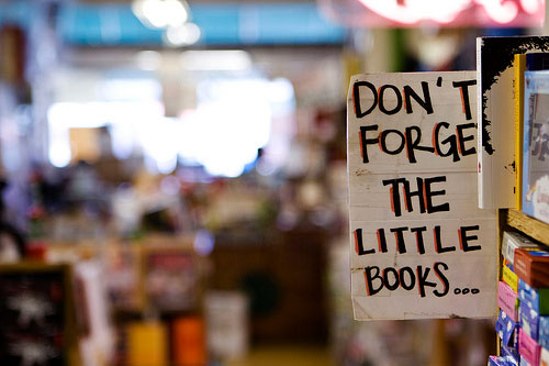 Sign reading Don't Forget the Little Books in used bookshop