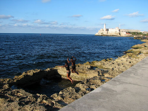 Coast in Havana with people jumping into the water holding hands