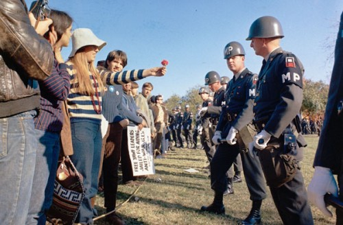 A female demonstrator offers a flower to military police on guard at the Pentagon during an anti-Vietnam demonstration.